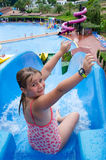 Happy young girl on tropical water slide Royalty Free Stock Image
