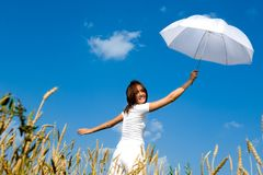 Happy young girl with umbrella in the field. stock photos
