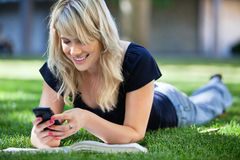 Happy young girl using cell phone. Smiling young college girl texting on a cell phone Royalty Free Stock Image