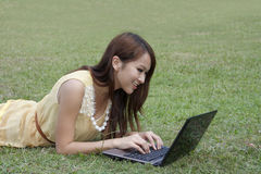 Happy young girl using laptop on grassland Stock Image
