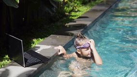 Happy young girl and using a laptop at the pool stock footage