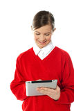 Happy young girl using tablet pc. Isolated over white background Stock Images