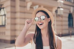 Happy young girl on vacation. She is in a stylish hat and sunglasses, wearing casual singlet, holding her spectacles, amazed stock images