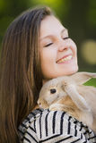 Happy young girl walking in spring, summer park with her bunny and smiling. Emotions of happiness. Stock Image