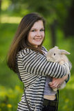 Happy young girl walking in spring, summer park with her bunny and smiling. Emotions of happiness. Stock Photo