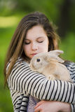 Happy young girl walking in spring, summer park with her bunny and smiling. Emotions of happiness. Royalty Free Stock Photography