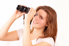 Happy young girl watches through binoculars Stock Images