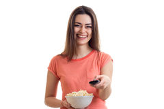 Happy young girl watching a tv with pop-corn Stock Images