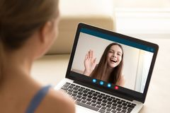 Happy young girl waving to girlfriend from laptop screen. Girlfriends chatting via video call application on computer. Long distance friendship, virtual Stock Photo