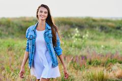 Happy young girl wearing blue jeans jacket and dress in the field. Happy smiling young girl wearing blue jeans jacket and white dress is standing in the field stock photos