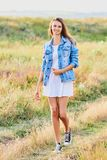 Happy young girl wearing blue jeans jacket and dress in the field. Happy smiling young girl wearing blue jeans jacket and white dress is standing in the field royalty free stock photos