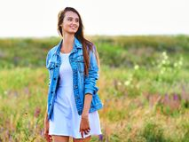 Happy young girl wearing blue jeans jacket and dress in the field. Happy smiling young girl wearing blue jeans jacket and white dress is standing in the field stock image