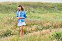 Happy young girl wearing blue jeans jacket and dress in the field. Happy smiling young girl wearing blue jeans jacket and white dress is standing in the field royalty free stock images
