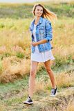 Happy young girl wearing blue jeans jacket and dress in the field. Happy smiling young girl wearing blue jeans jacket and white dress is standing in the field royalty free stock photo