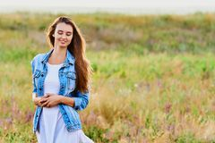 Happy young girl wearing blue jeans jacket and dress in the field royalty free stock photos
