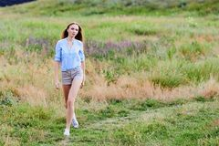 Happy young girl wearing blue jeans jacket in the field. Happy smiling young girl wearing blue jeans jacket and shorts is standing in the field royalty free stock images