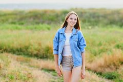 Happy young girl wearing blue jeans jacket in the field. Happy smiling young girl wearing blue jeans jacket and shorts is standing in the field stock images