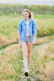 Happy young girl wearing blue jeans jacket in the field. Happy smiling young girl wearing blue jeans jacket and shorts is standing in the field stock photo