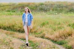 Happy young girl wearing blue jeans jacket in the field. Happy smiling young girl wearing blue jeans jacket and shorts is standing in the field royalty free stock photography