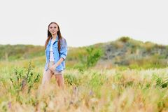 Happy young girl wearing blue jeans jacket in the field. Happy smiling young girl wearing blue jeans jacket and shorts is standing in the field royalty free stock photos