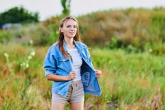 Happy young girl wearing blue jeans jacket in the field. Happy smiling young girl wearing blue jeans jacket and shorts is standing in the field royalty free stock photo