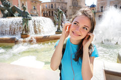 Happy Young girl wearing headphones listening to music traveling in Valencia, Spain. Royalty Free Stock Image