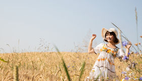 Happy young girl in a wheat field with background. Stock Photography