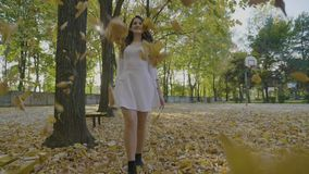 Happy young girl in white clothes walking in the park admiring falling autumn yellow leaves and enjoying freedom. In slow motion stock video