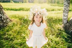 Happy young girl with a wreath of flowers on her head and a white dress smiling happily Stock Image