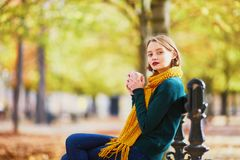 Happy young girl in yellow scarf walking in autumn park stock image