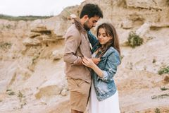 Happy young girlfriend and boyfriend hugging. In sand canyon royalty free stock photography