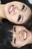 Happy young girls. Closeup portrait of happy young girls lying on ground with their heads together royalty free stock photography