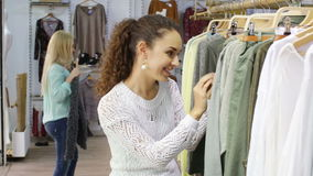 Happy young girls choosing new clothes in shop stock video