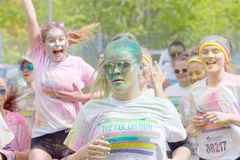 Happy young girls covered with color powder running Royalty Free Stock Photo