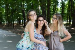 Three beautiful young boho chic stylish girls walking in park. royalty free stock photos