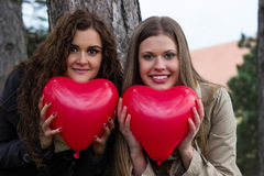 Happy young girls holding a red heart in the hands stock photo