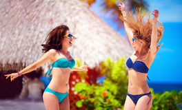 Happy young girls jumping on tropical beach, summer vacation Royalty Free Stock Photo