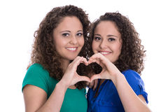 Happy young girls making heart with hands: real twin sisters. Royalty Free Stock Photography