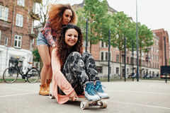 Happy young girls playing with longboard Stock Image