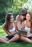 Happy young girls with a tablet computer Stock Images