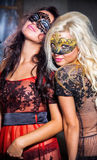 Happy young girls under masks on the party Stock Images