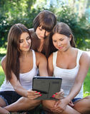 Happy young girls using a tablet computer Stock Photo