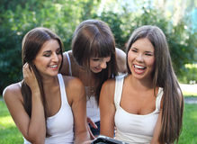 Happy young girls using a tablet computer Royalty Free Stock Image