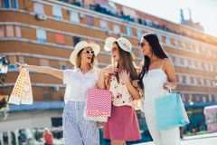 Young girls walking the street with shopping bags. Happy shopping with smiles royalty free stock image