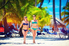 Happy young girls walking on tropical beach, during summer vacation Stock Image