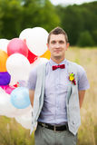 Happy young groom holding in hands colorful latex balloons Royalty Free Stock Images