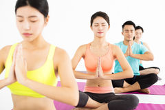 Happy young Group  doing yoga exercises Royalty Free Stock Images
