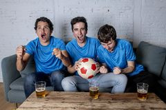 Young group of happy and excited men watching a football game on the couch. Happy young group of football fans caucasian men watching the football and Stock Images