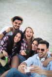 Happy young group of people taking selfies on beach. In summer royalty free stock photos