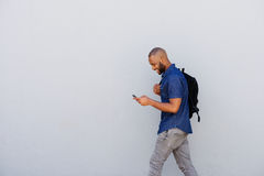 Happy young guy with bag walking with mobile phone. Side portrait of a happy young guy with bag walking outdoors and sending text message by mobile phone Stock Photography